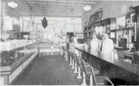 The Dick Schultz' Store, son Harry and Mrs. Minnie Kennedy behind counter, 1933