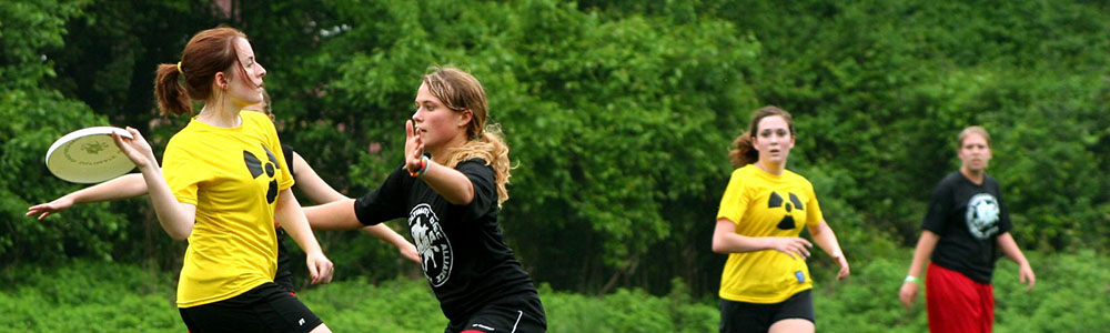 Five women playing ultimate frisbee. Woman on the left getting ready to pass to teammate in yellow shirt