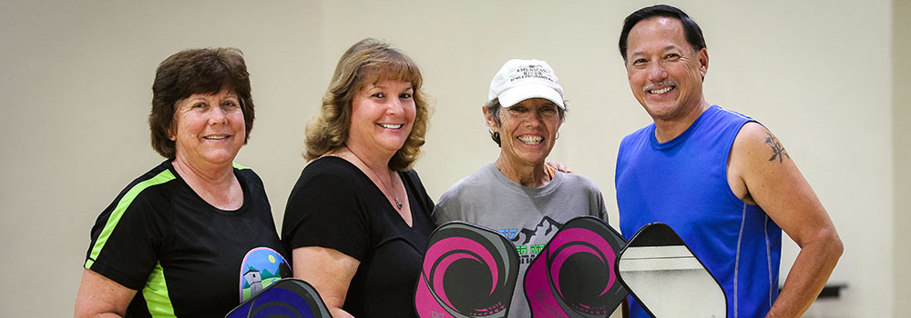 Three women and one man stand in group smiling while holding Pickleball rackets