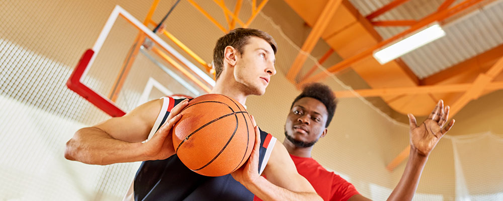 Man with basketball in hand looking to right, being gaurded by opposing man