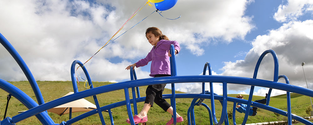 Young girl walking across playground structure at Cayetano Park with colorful balloons