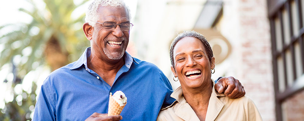 A laughing, graying couple walk around town. Husband has arm wrapped around wife with ice cream cone in his hand