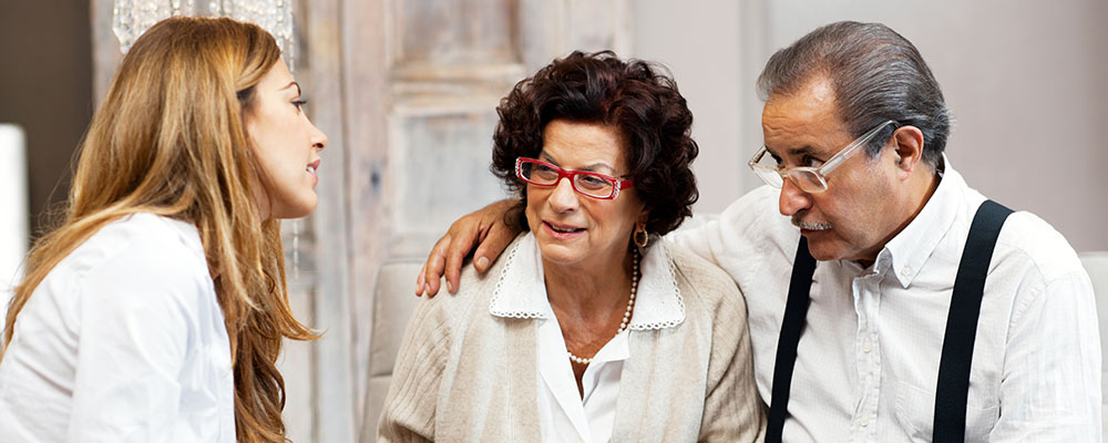 Woman assisting concerned senior couple, man with his arm around wife in red glasses