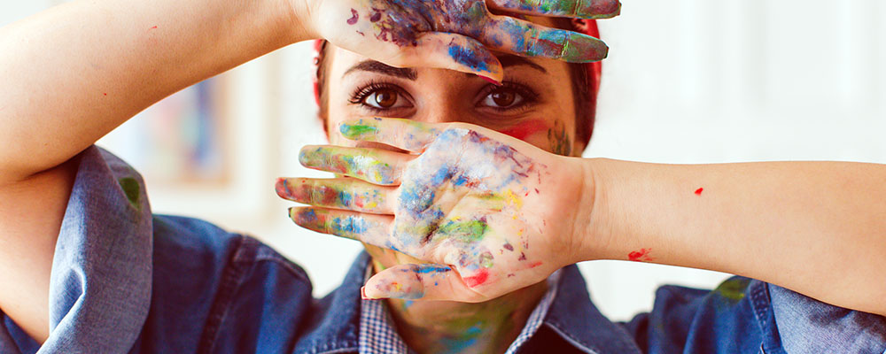 Woman with hands covered in paint covering face, brown eyes looking at the camera