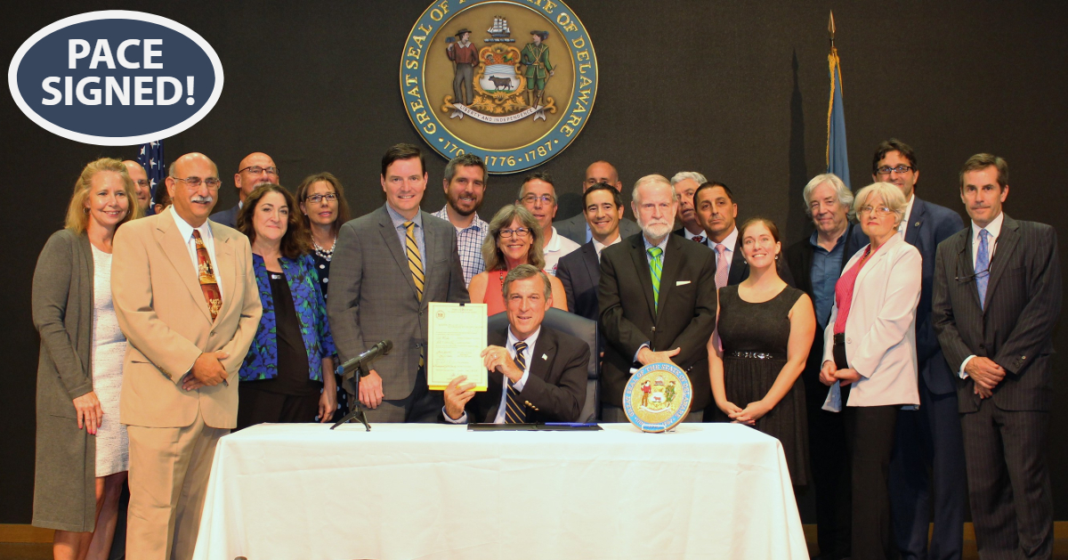 Governor John Carney holds up signed PACE legislation
